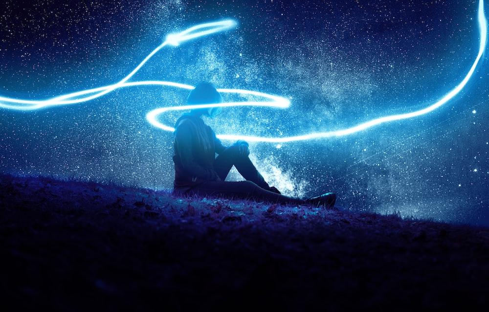 person sitting under blue LED lights