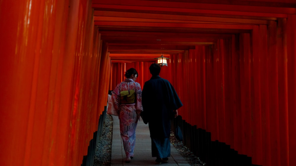 two person wearing traditional dresses walking on hallway