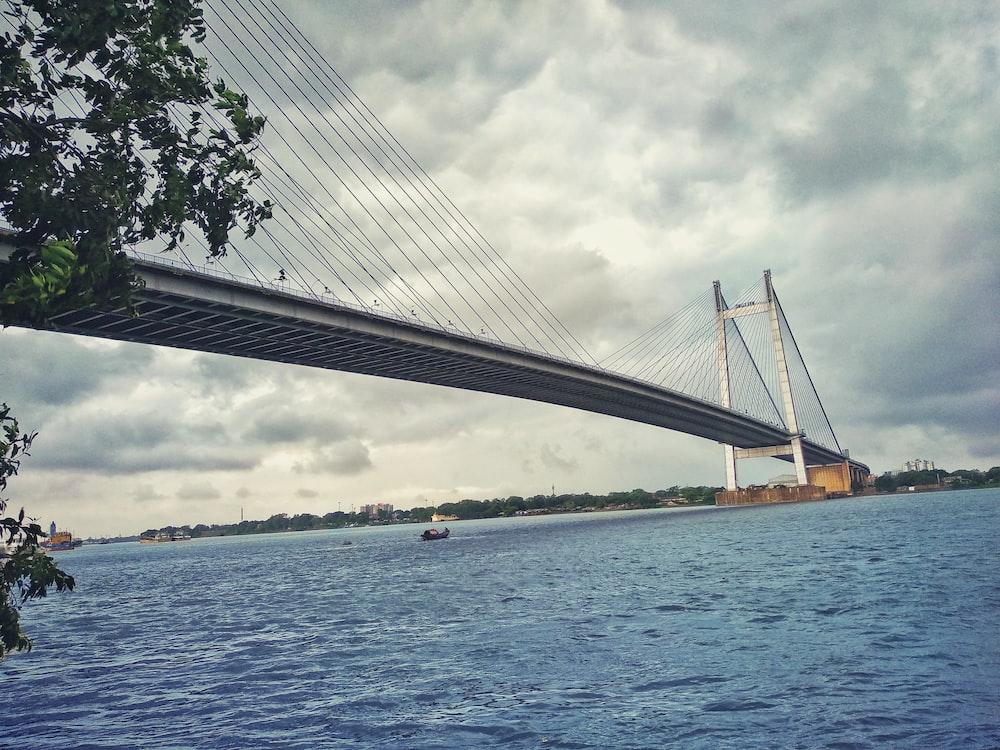 gray concrete bridge under nimbus clouds
