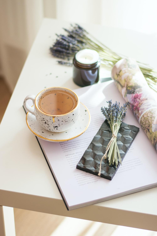 white ceramic cup beside flower