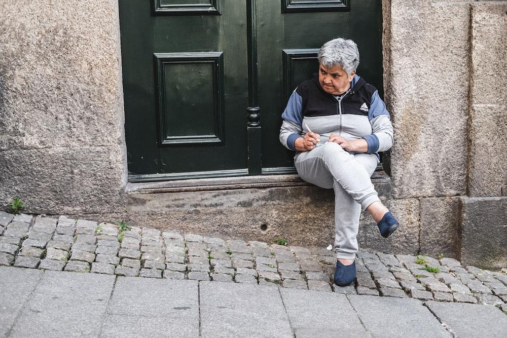 unknown person sitting near black wooden door