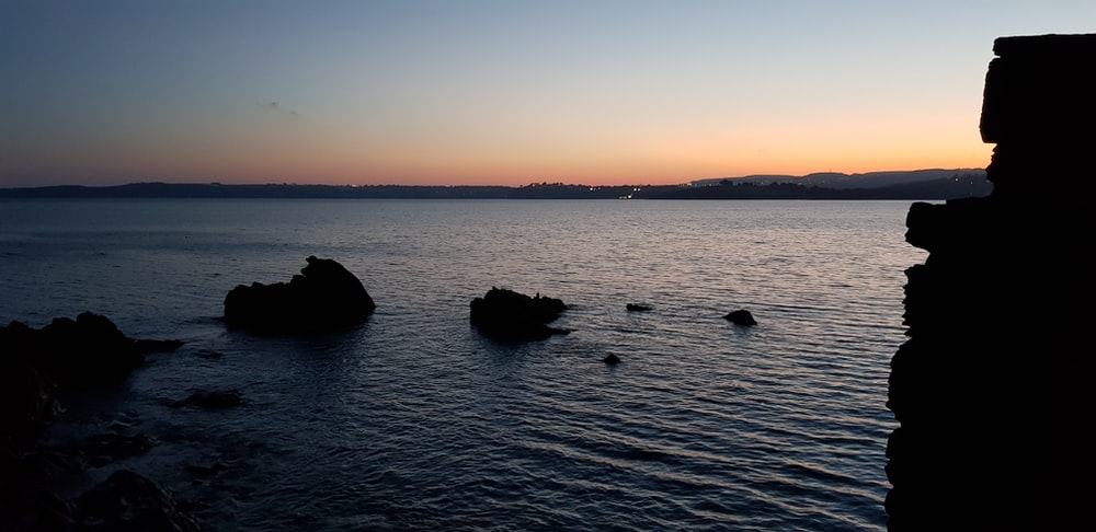 silhouette of rock formation at the shore