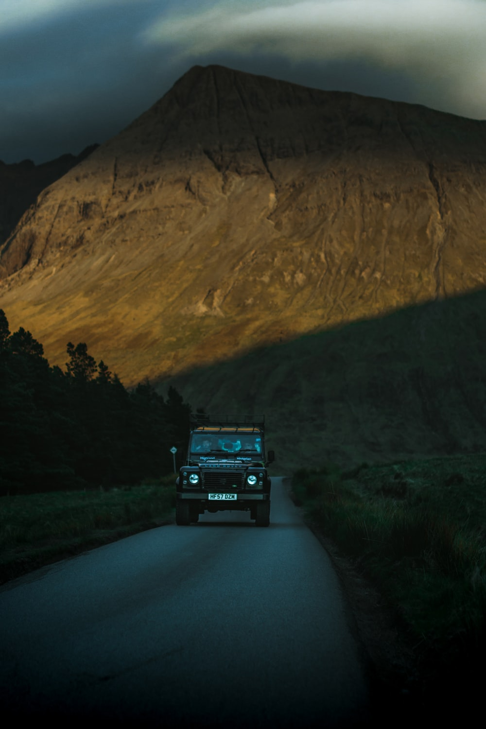 grey Land Rover Defender in country road