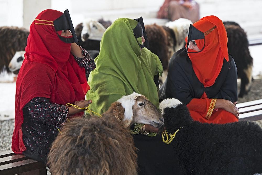 three people wearing red, orange, and green niqab headdress