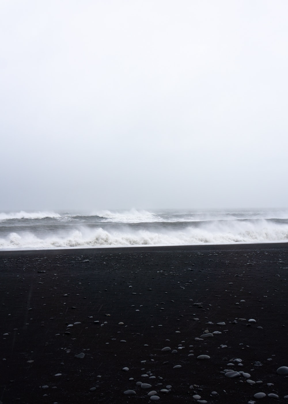 black sand and ocean waves under fogs