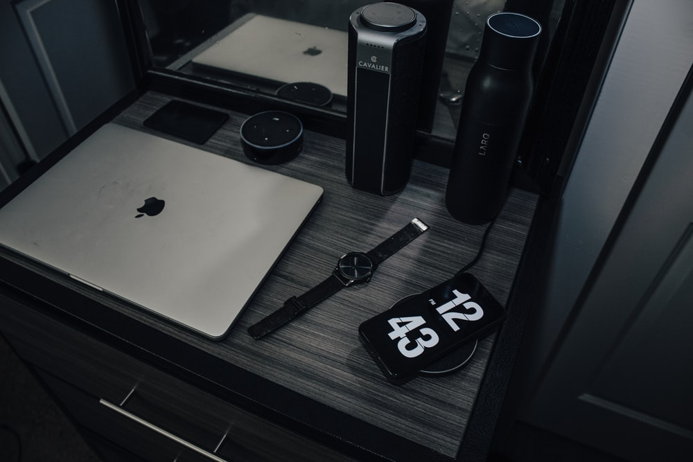 Apple MacBook Air, analog watch and black smartphone on table
