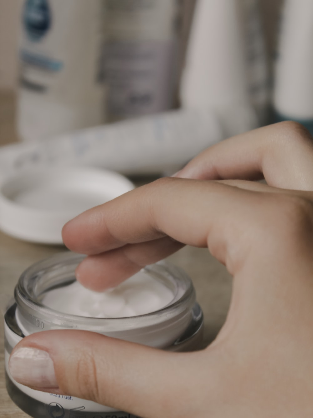 person's finger touching white cosmetic cream