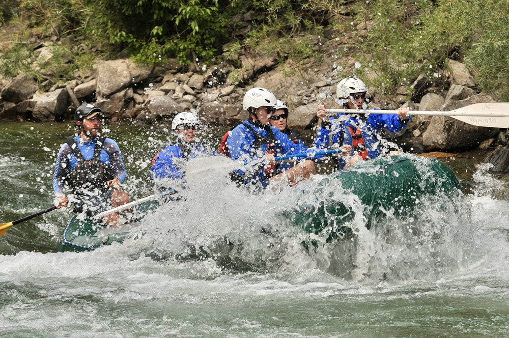 five people rafting on river