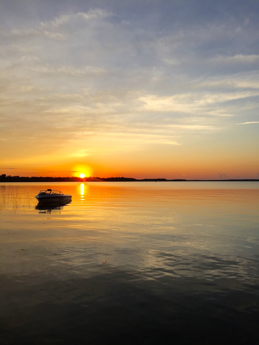 boat adrift away from shore during sunset