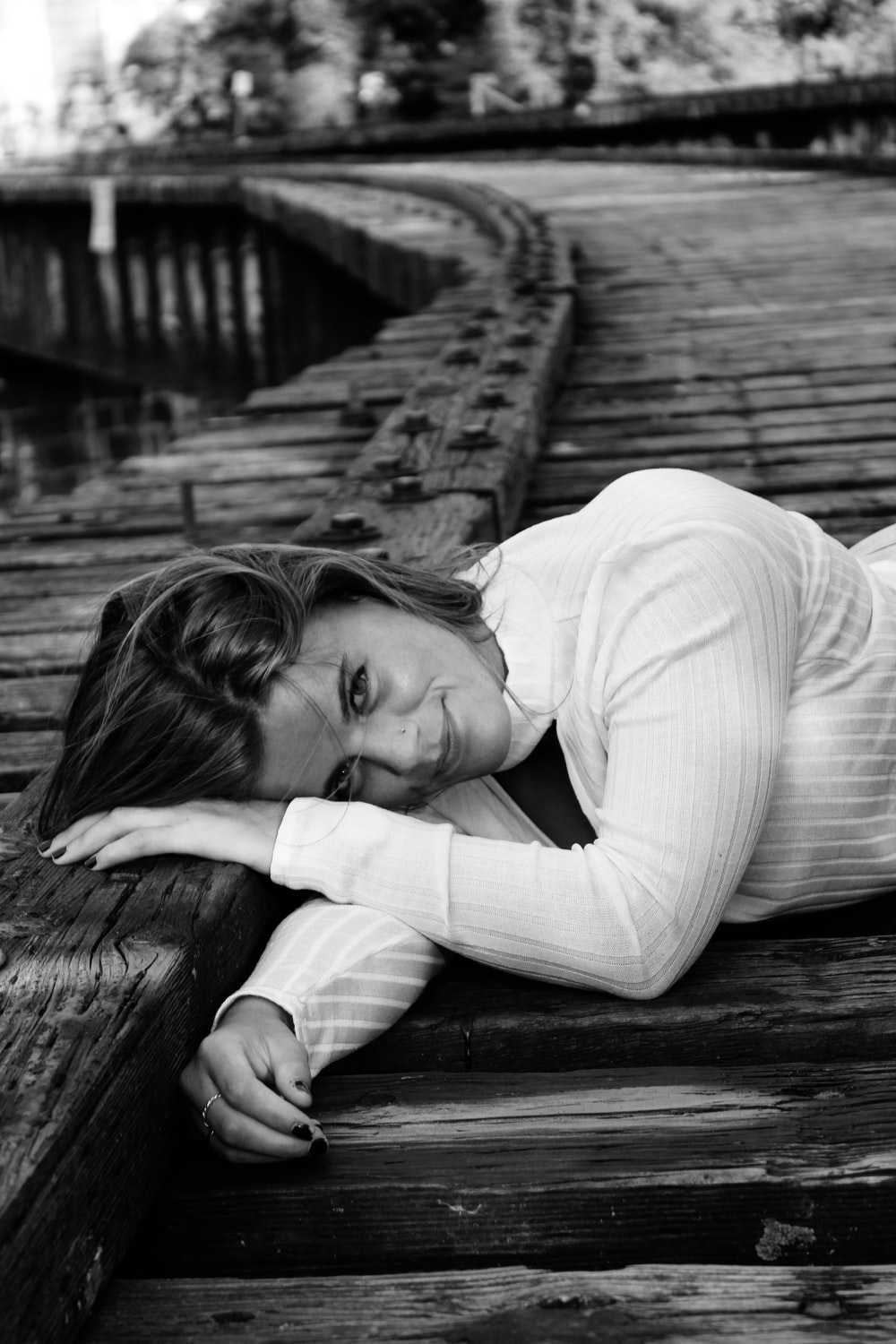 grayscale photography of woman lies near fence