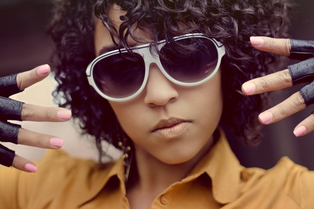 woman wearing sunglasses and showing both hands