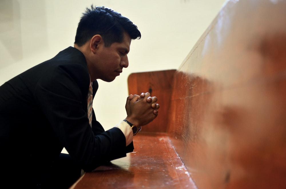 man sitting, closing his eyes and praying