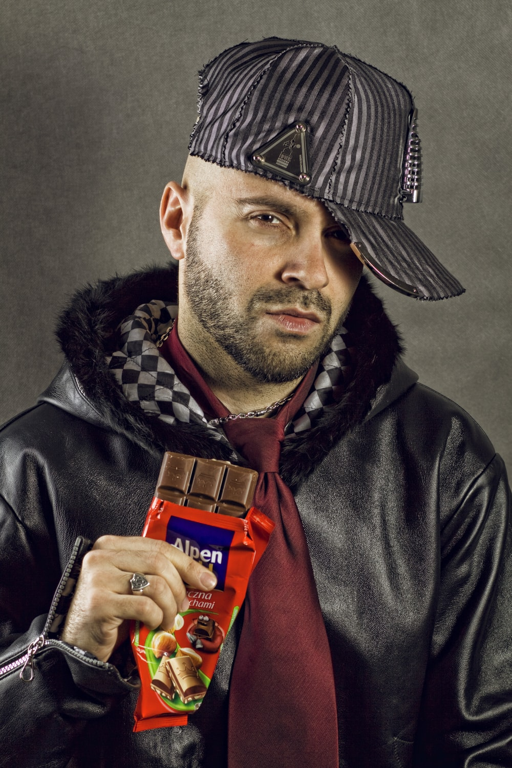 man in black leather jacket with red Alpen chocolate bar pack in hand