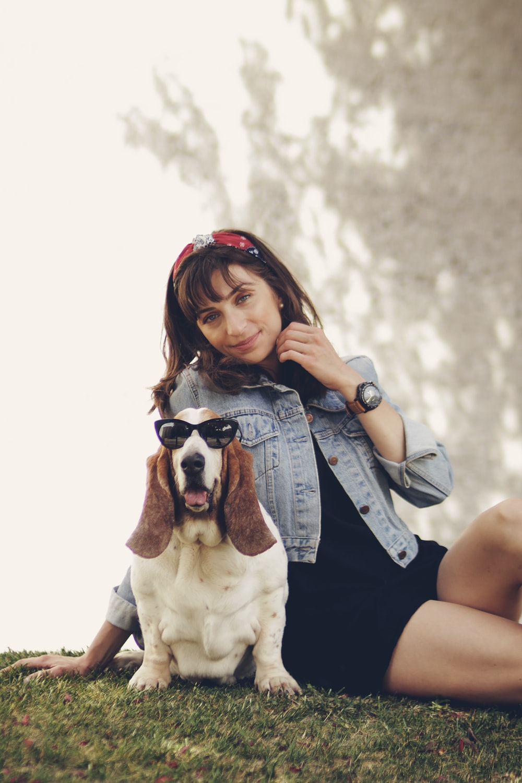 woman sitting beside the basset hound