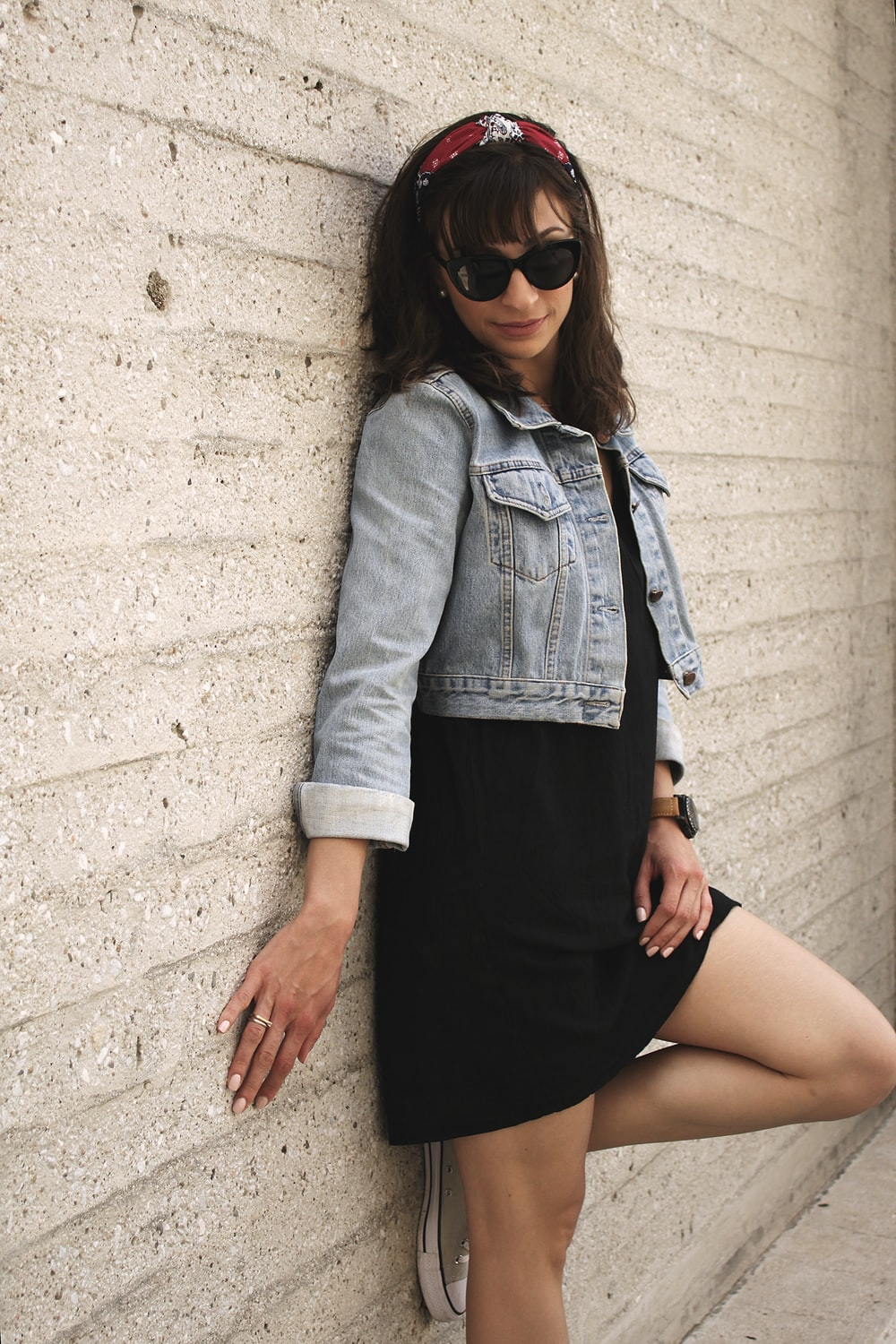 woman leaning on white concrete wall during daytime