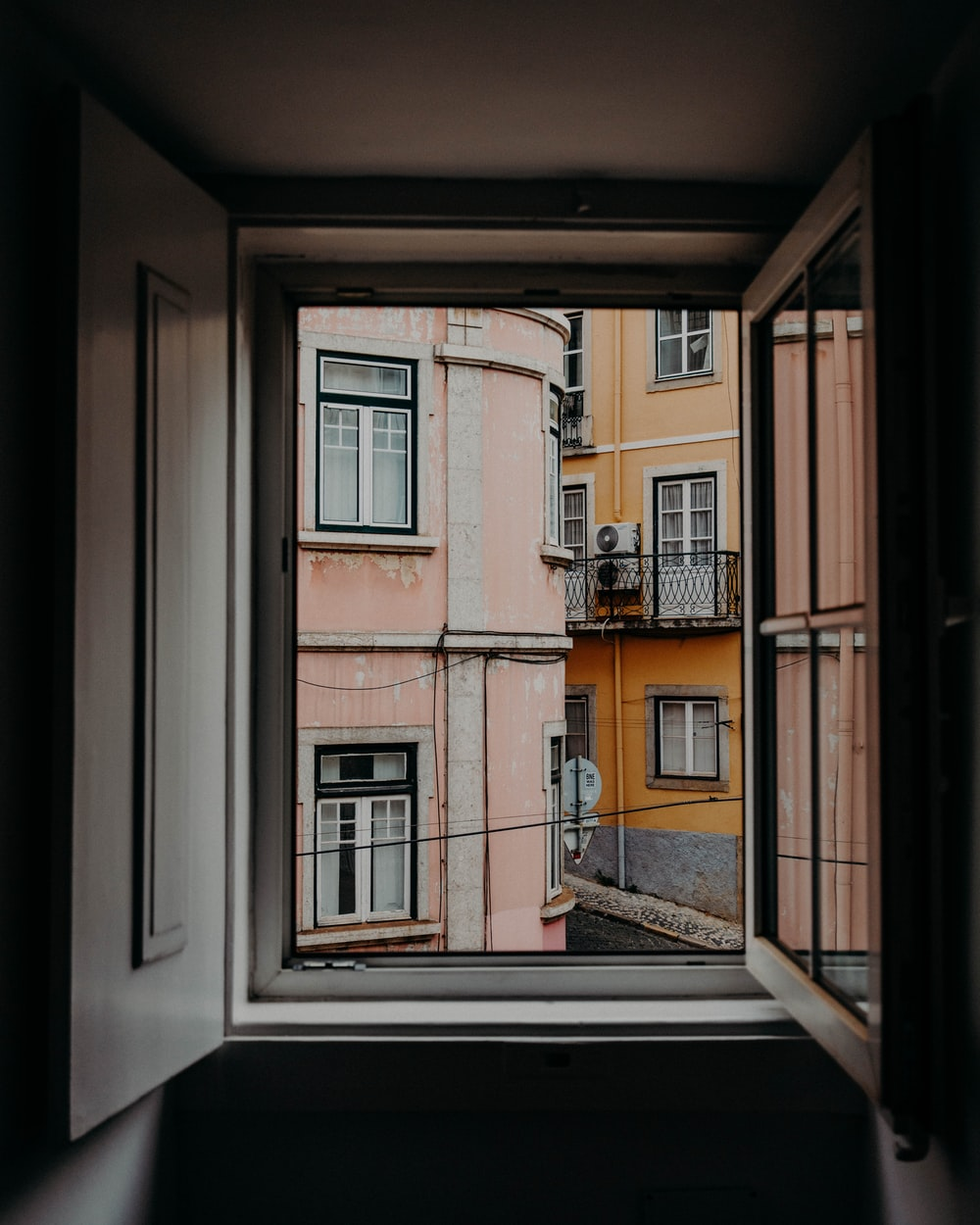 wooden window opened with view of concrete buildings