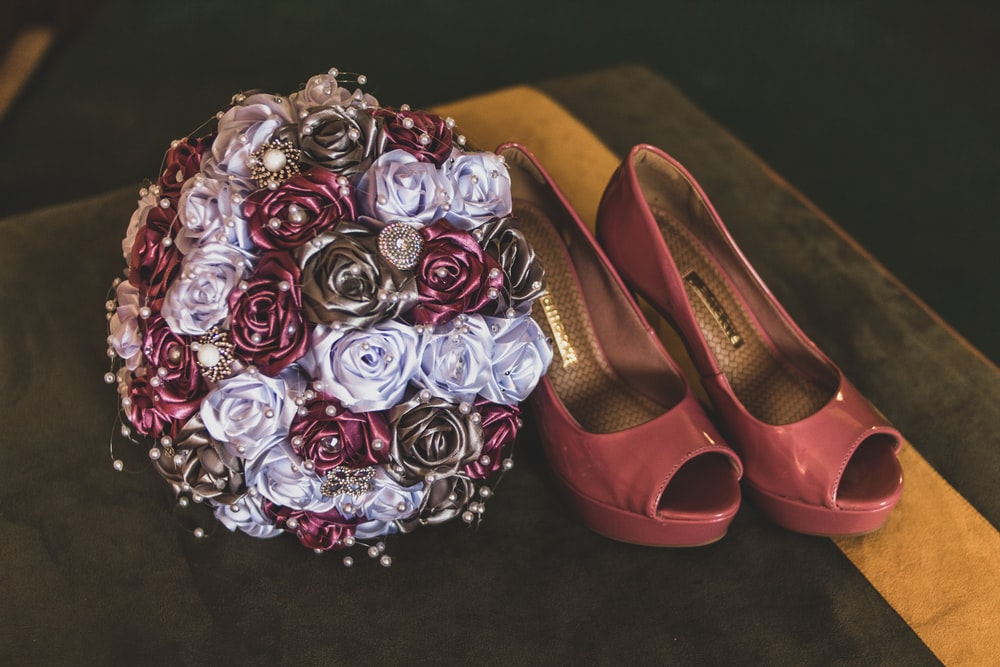 pair of maroon leather shoes beside flower boquet