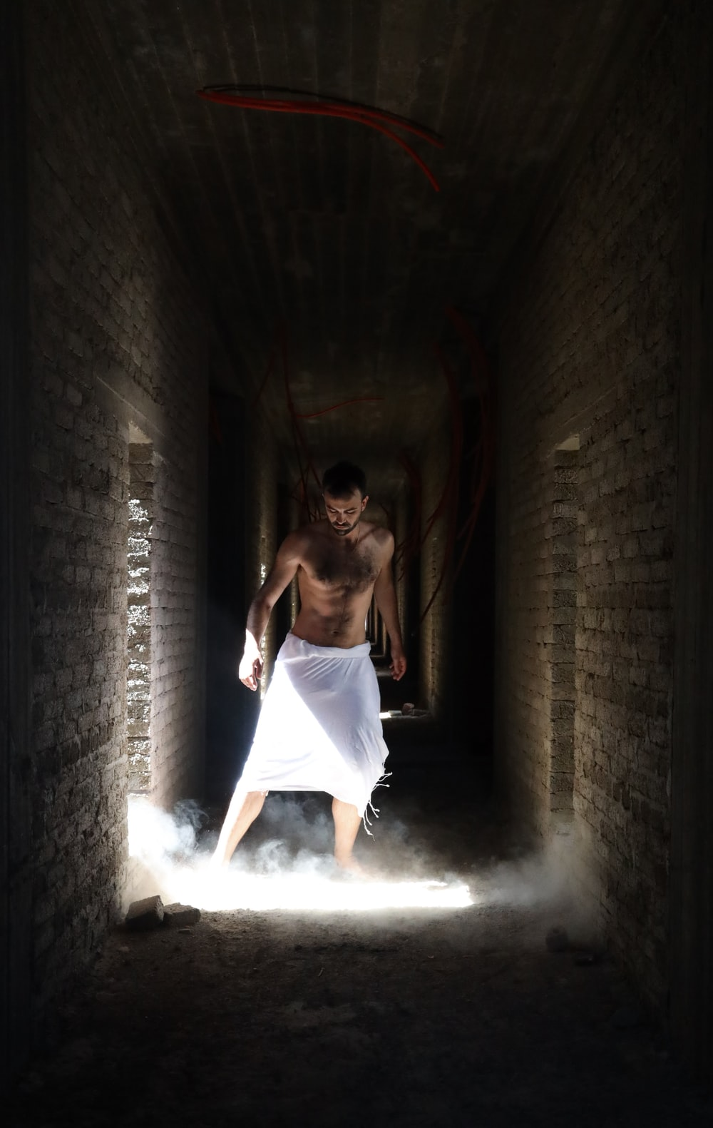 man wearing white shirts in the middle of hallway