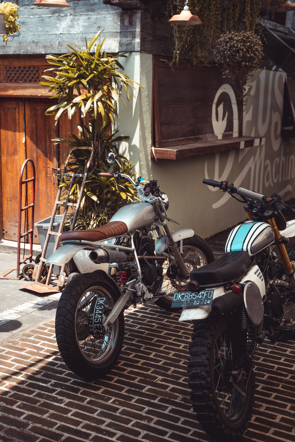 two standard motorcycles near hand truck