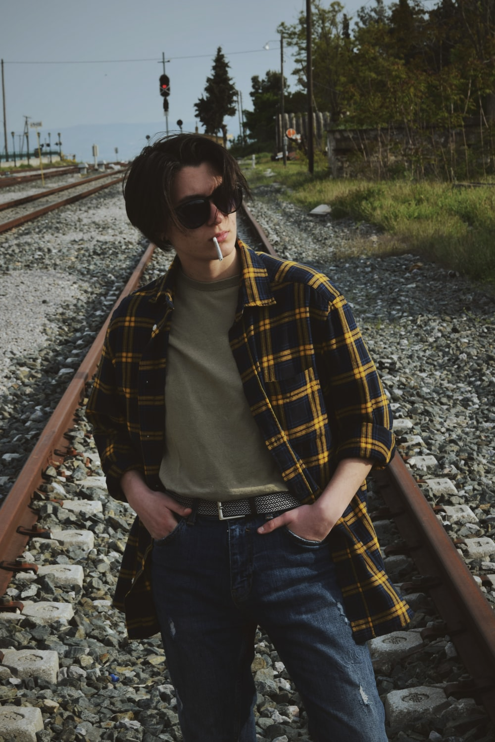 man with cigarette in black and brown checked blazer and blue denim jeans standing in train tracks