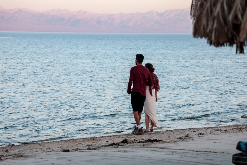 male and female standing on beach