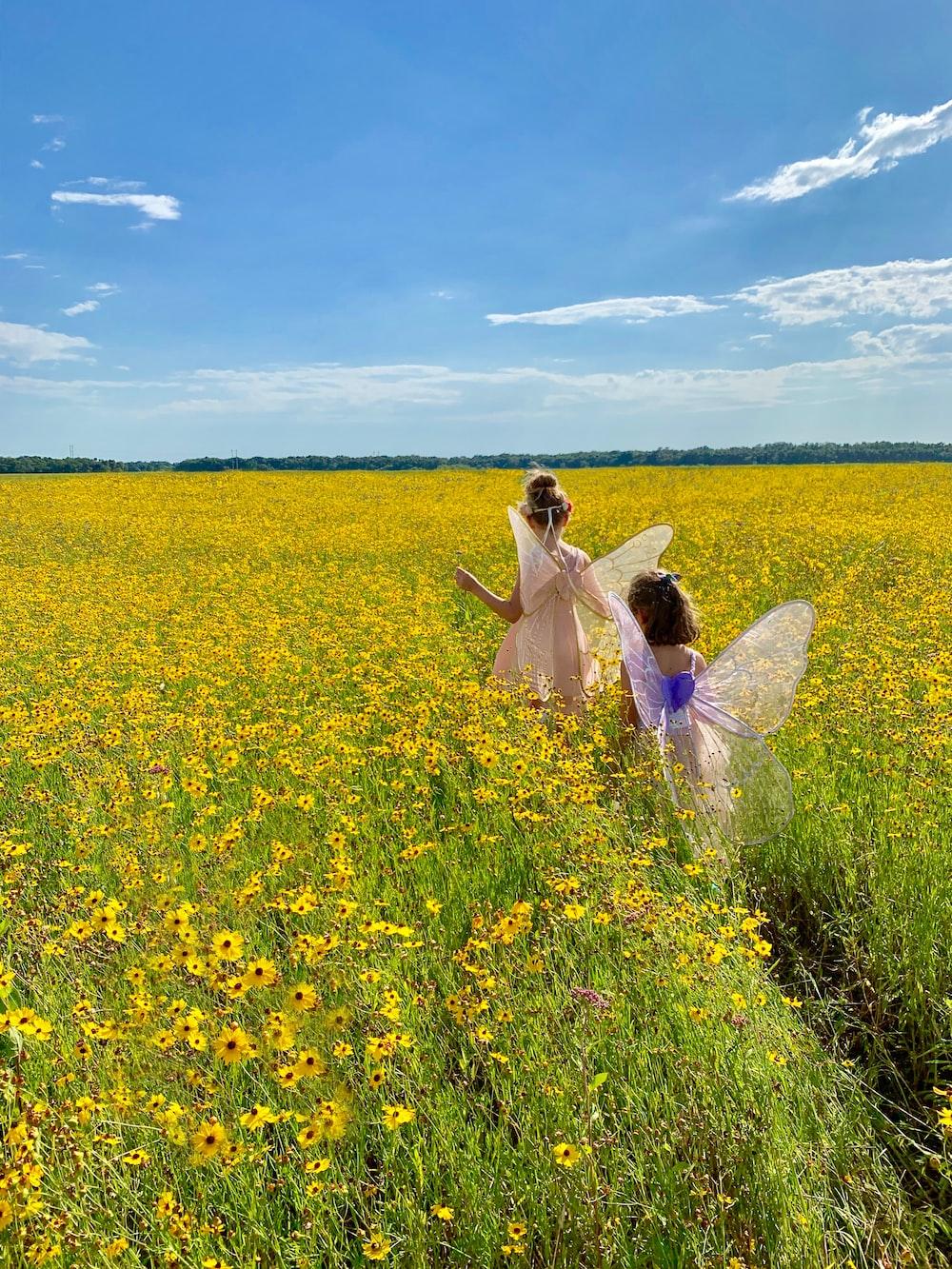 two girl's wearing fairy dresses walking in yellow flower fields