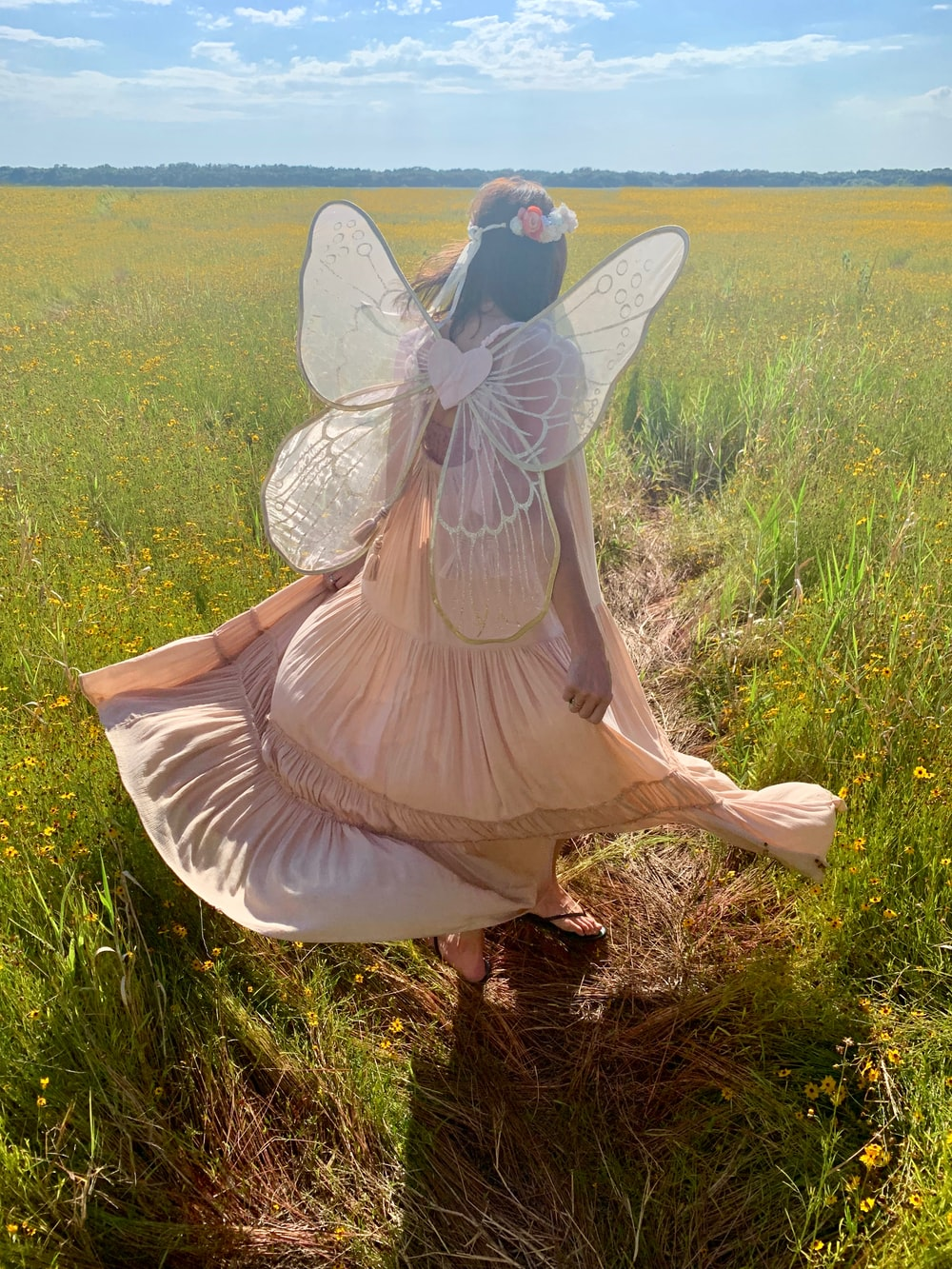 woman in fairy costume standing on green field