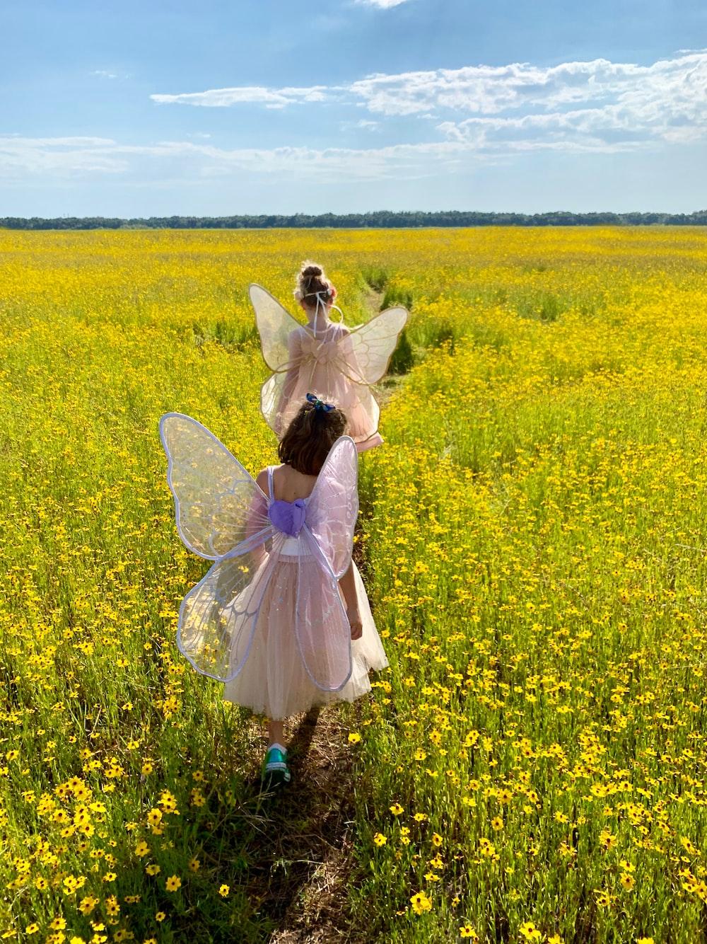 two girls walking near flower field