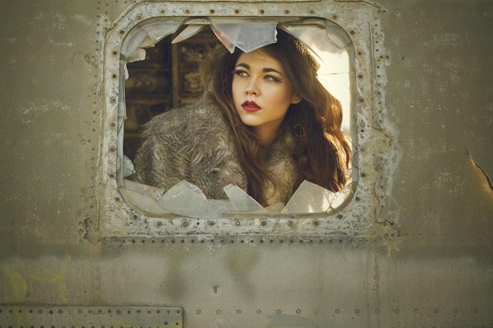 woman seated near broken glass window