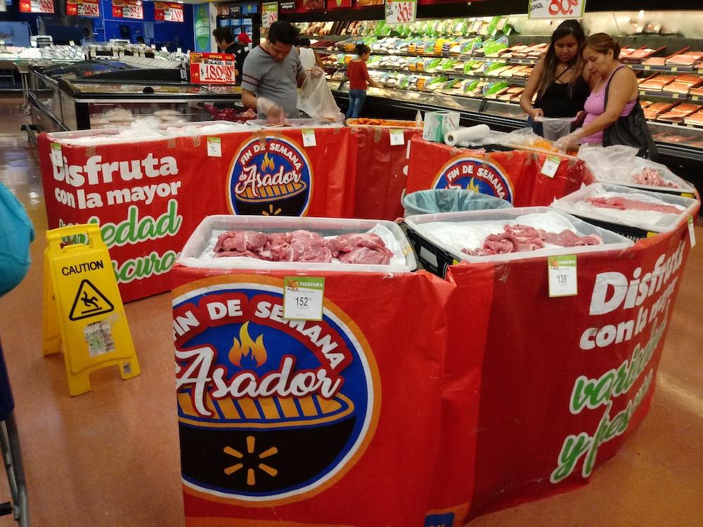 people standing beside raw meats in side market