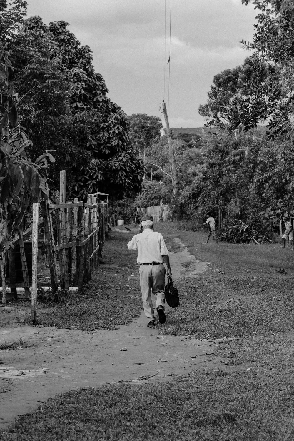 man walking beside fence near trees