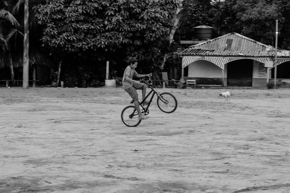 grayscale photo of boy doing exhibition with bike