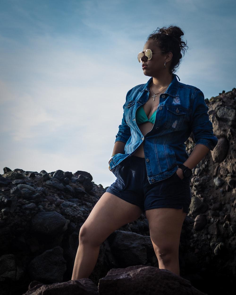 woman in blue button-up t-shirt standing near rocks