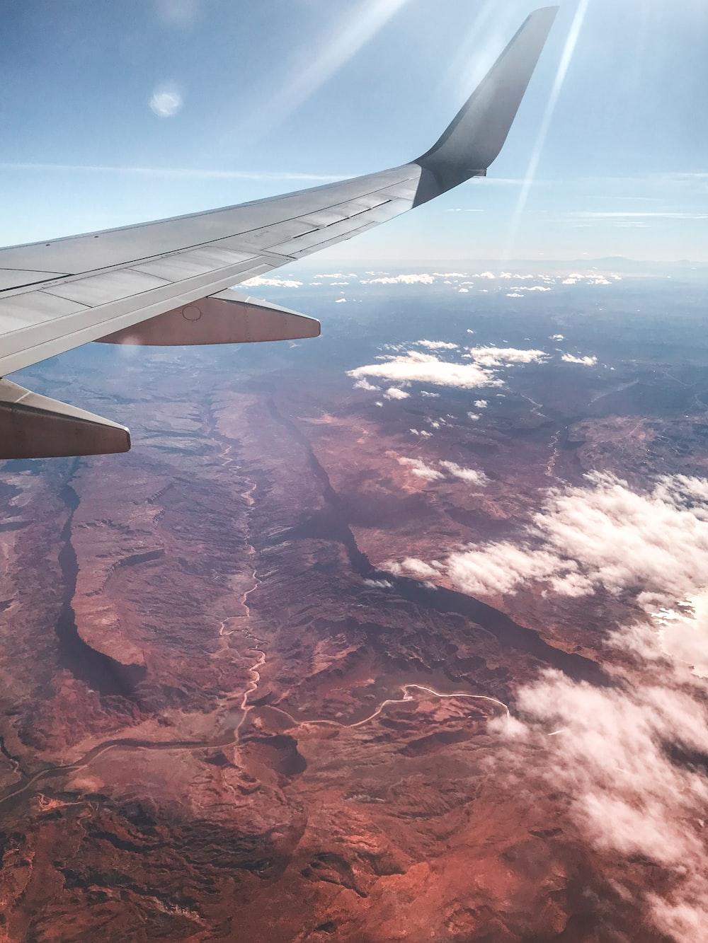 white airliner flying on sky during daytime