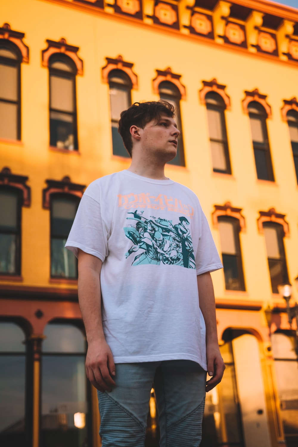 man in white and green crew-neck t-shirt standing near building