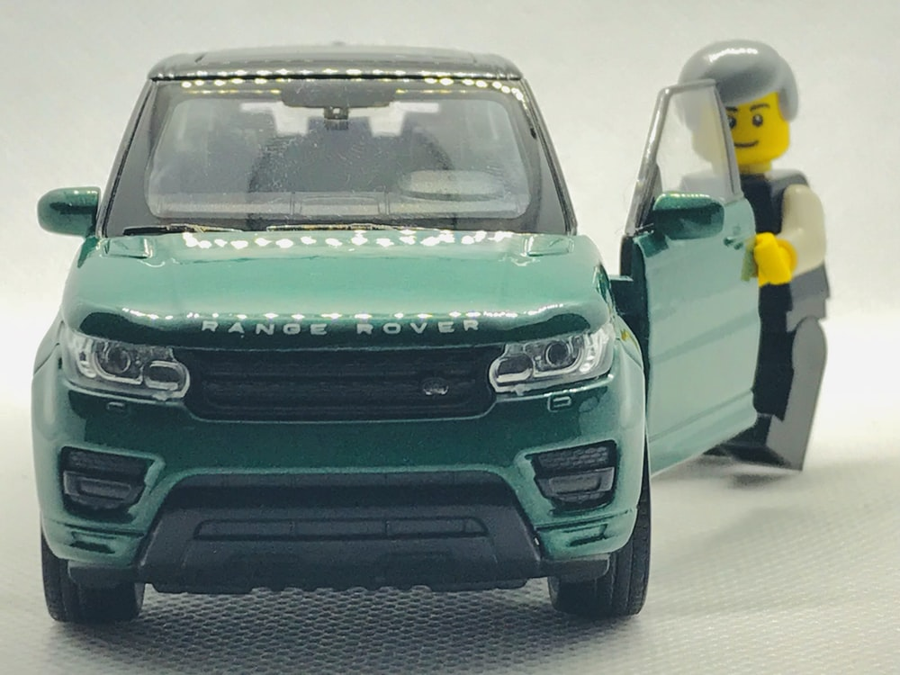 green Range Rover SUV scale model with minifig standing at open door