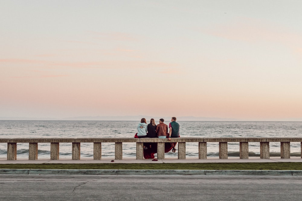four people sitting on concrete bench facing body of water