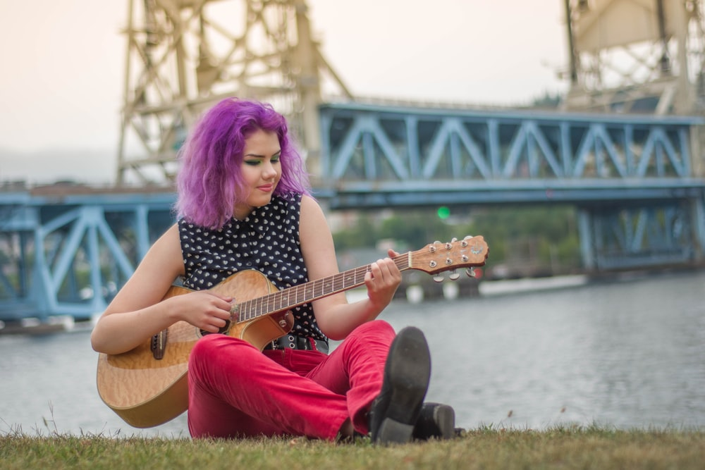 woman wearing black shirt sitting on grass while playing guitar
