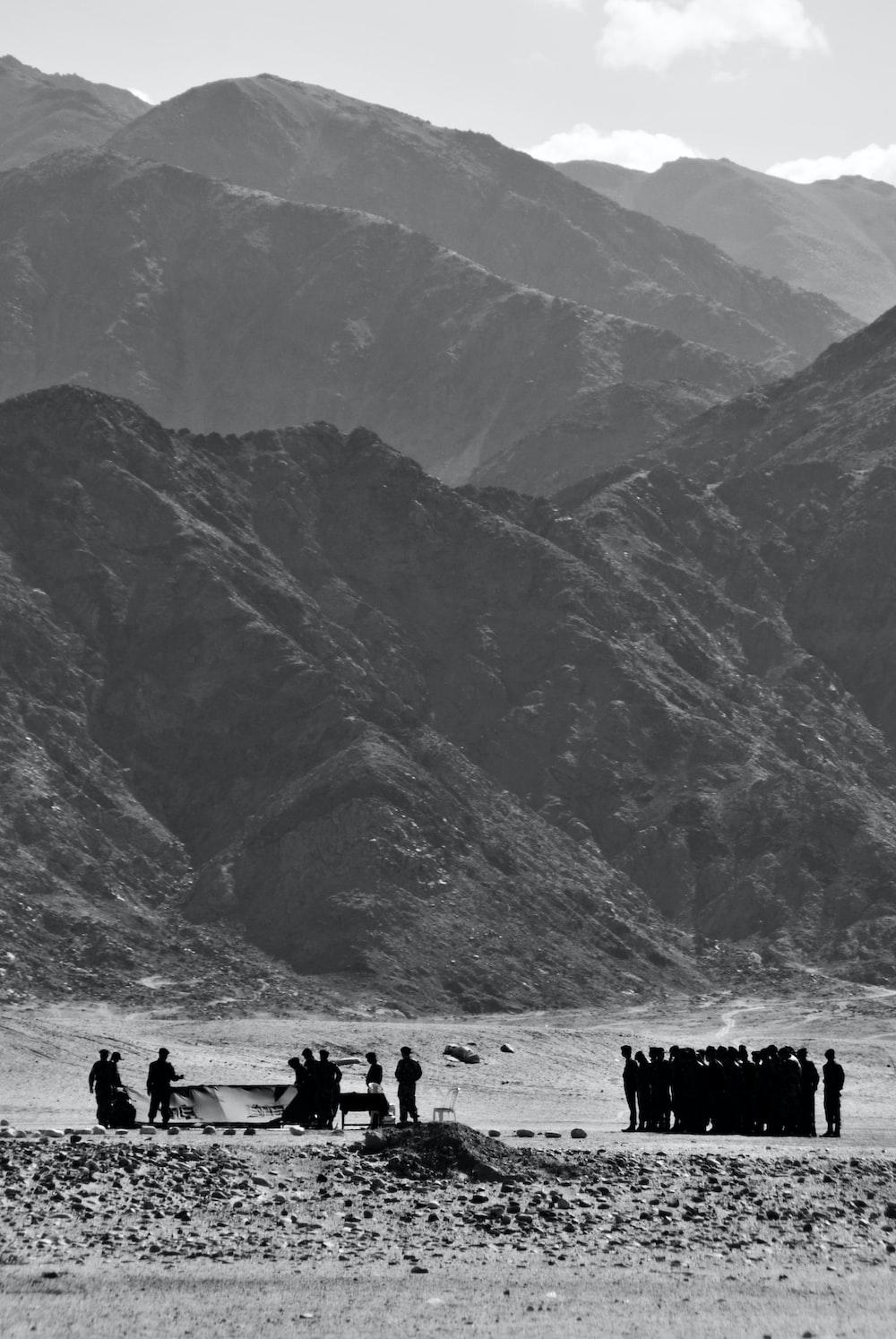 grayscale photo of people gathering near mountain