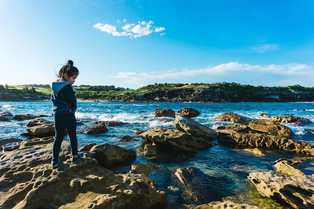 girl standing on rock near river