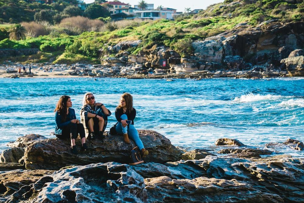 three women sitting on rocks near river