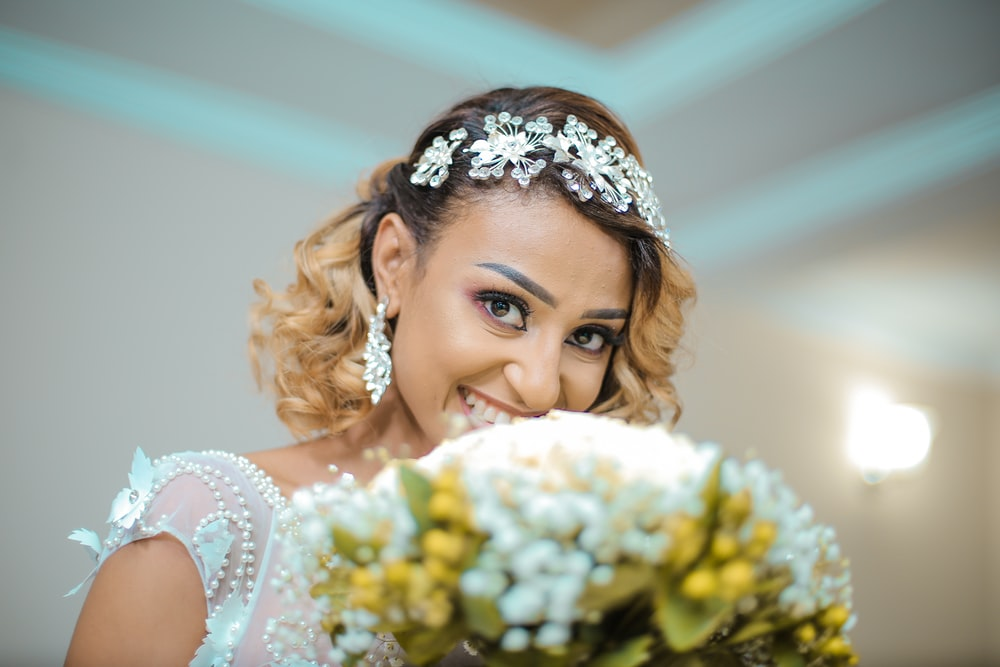 smiling woman in white wedding dress with bunch of white flowers