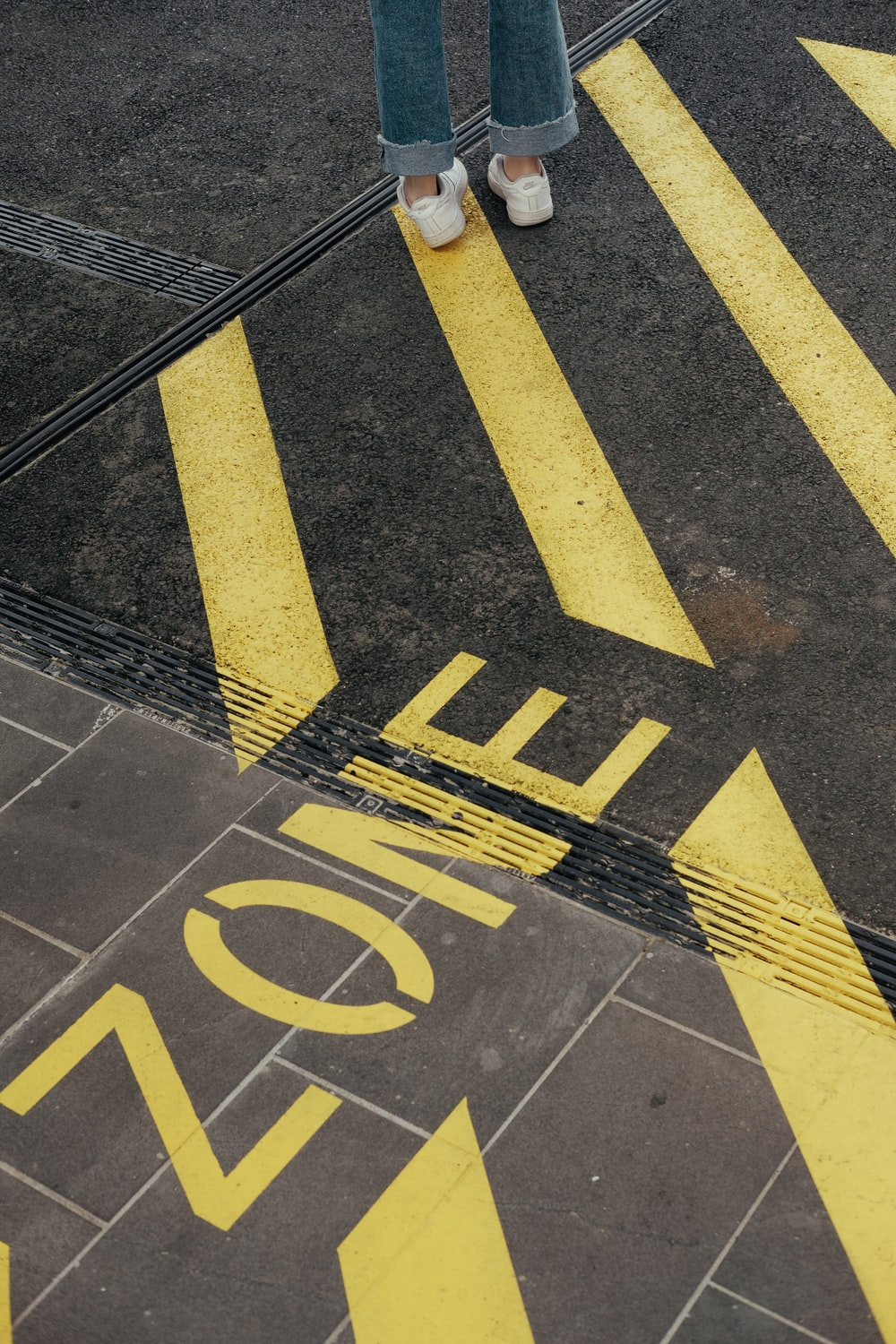 person standing on yellow stripe sign on orad