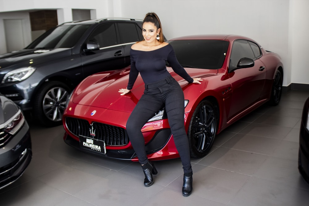 woman leaning on red Maseratti car