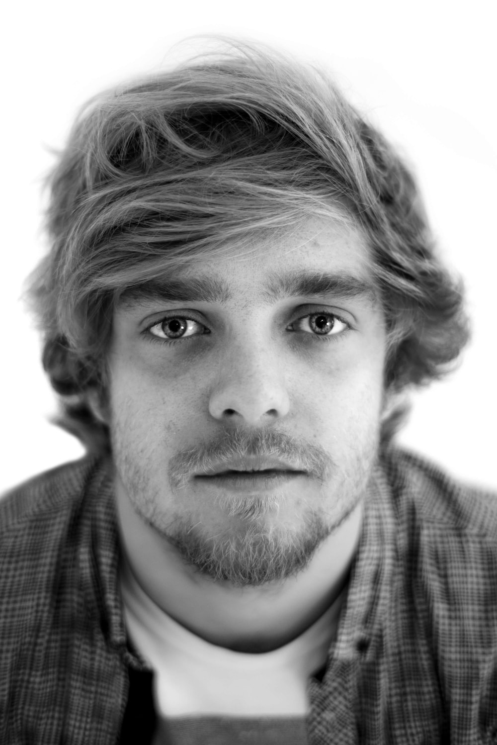 grayscale photo of man in flannel shirt