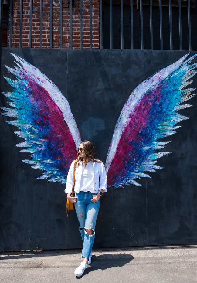 woman standing near wing graffitti