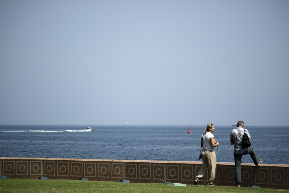 two people standing near body of water