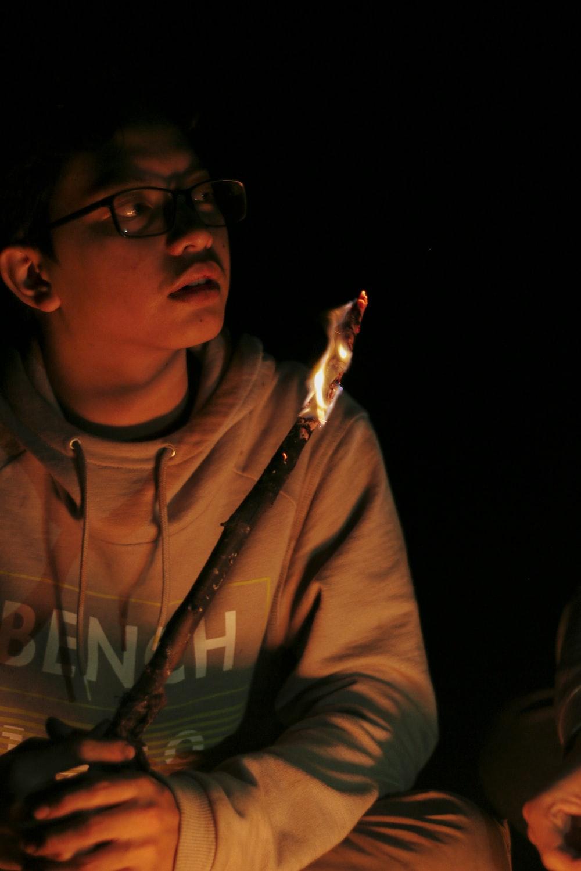 man wearing hoodie holding torch