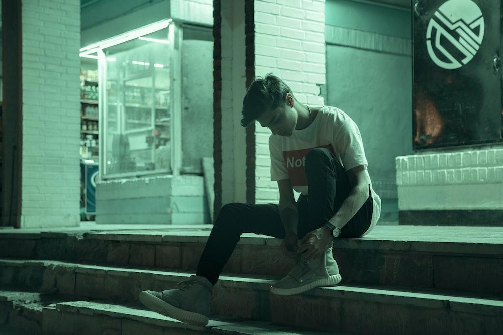 man sitting on stairway during nighttime