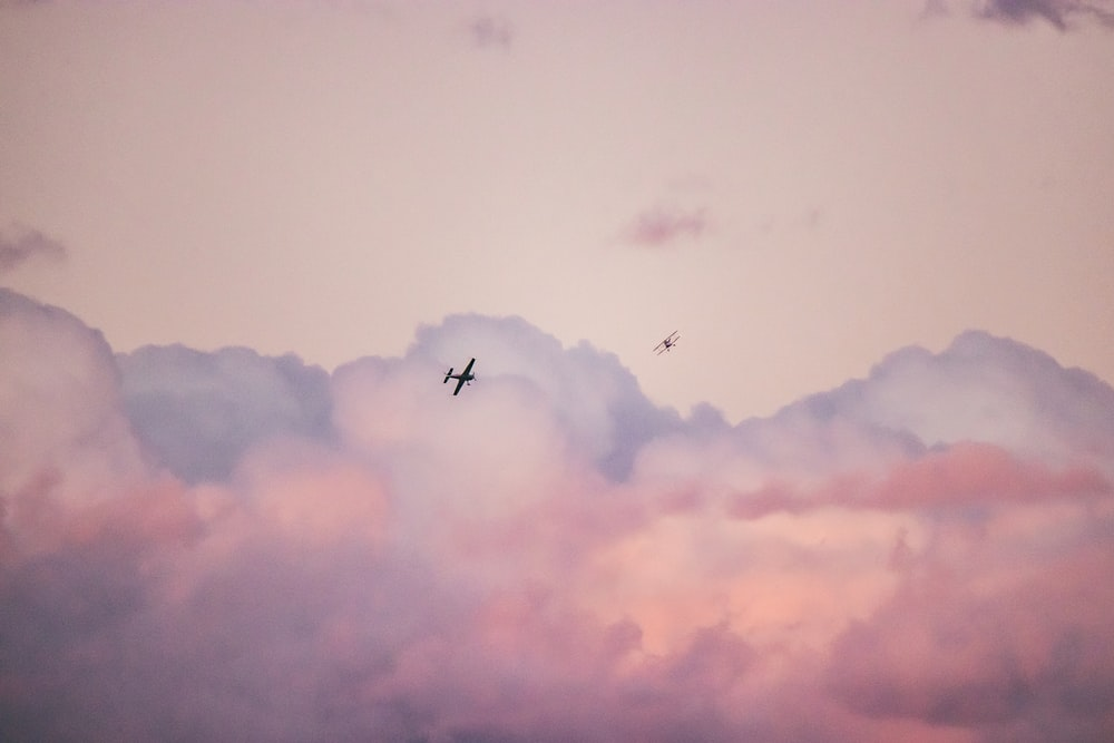 silhouette photography of airplane during flight during daytime